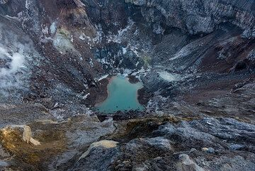 The NW crater of Gorely, site of the most recent episode of unrest at the volcano during 2013-14 when a vent next to the small acid lake was emitting a hot jet of incandescent gas (at 900 deg temperatures). Now, it is calm again, but for how long? (Photo: Tom Pfeiffer)