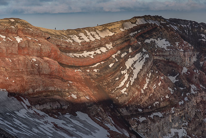 Evening light shining on the reddish lava layers of the inner crater walls. It is time to descend! (Photo: Tom Pfeiffer)