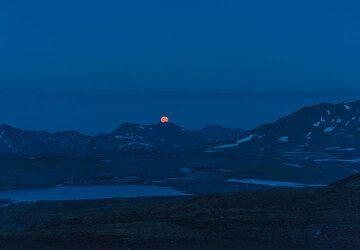 A brilliant orange moonrise over the eastern horizon's mountain peaks. (Photo: Tom Pfeiffer)