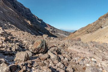 The trail is mostly over glacial moraine and debris avalanche ground through the large valley that breaches the summit area towards the NE. (Photo: Tom Pfeiffer)