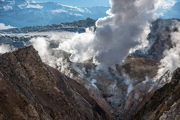 View of a strong fumarole in the crater wall beneath the massive glacier occupying the southern part of the crater visible in the background. (Photo: Tom Pfeiffer)