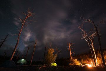 Campfire at night while waiting for clear skies. (Photo: Tom Pfeiffer)