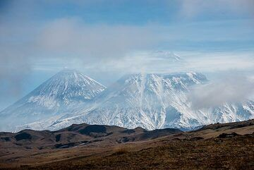 Light fog hovers over the plain, with Klyuchevskoy and Kamen behind. (Photo: Tom Pfeiffer)