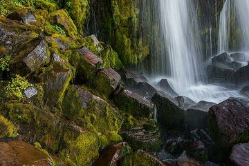 The polished rocks and broken-off pieces reveal columnar structures formed by the slow cooling of an ancient lava flow, now cut by the waterfall. (Photo: Tom Pfeiffer)