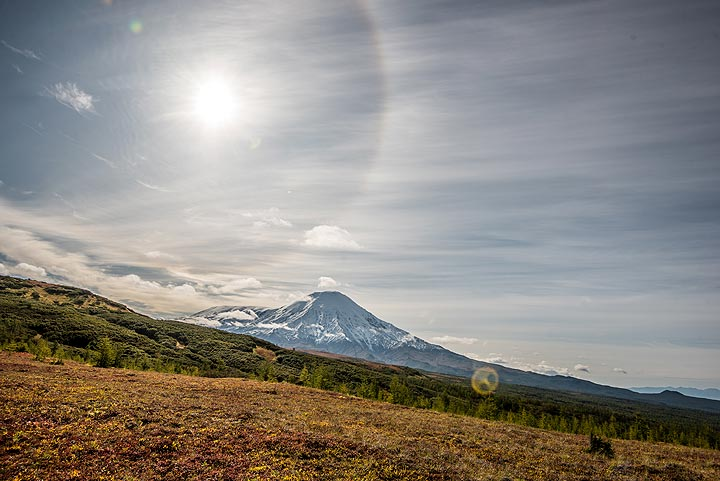 A halo is visible around the sun above Tolbachik volcano - a storm is approaching from SW and sends its first messengers, thin veils of high clouds. (Photo: Tom Pfeiffer)