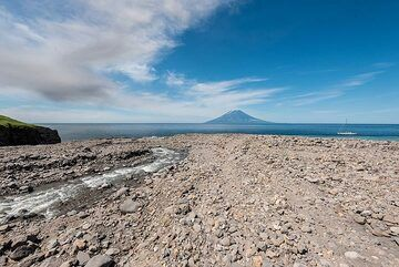 The mouth of the creek forms a vast pebble beach. The ash plume from the eruption in the previous picture is seen drifting NW towards Alaid. (Photo: Tom Pfeiffer)