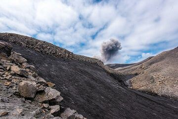On our way up one of the last ridges, we see an ash plume from another eruption, which were occurring about once every hour. (Photo: Tom Pfeiffer)