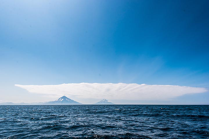 As we approach Paramushir Island, the tall peaks of Chikurachki (l) and Fuss (r) volcanoes come into view. (Photo: Tom Pfeiffer)