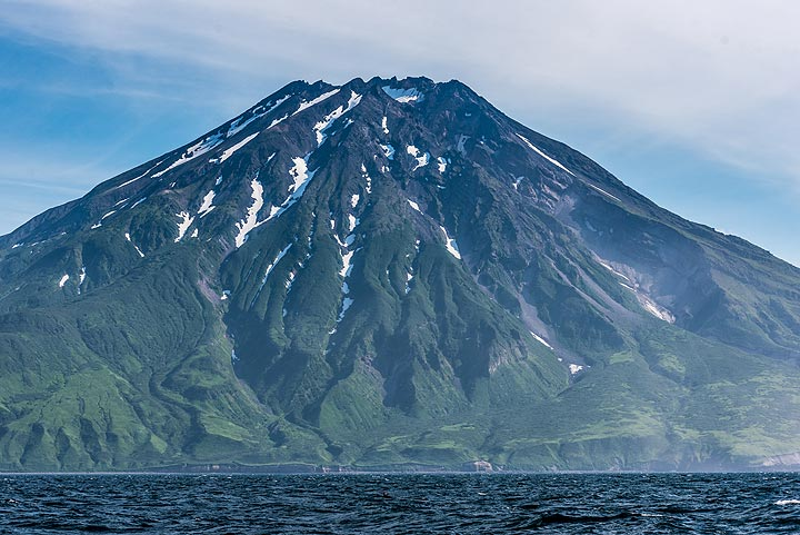We approach the southern part of Paramushir, dominated by Fuss stratovolcano (1772 m) which forms a peninsula. (Photo: Tom Pfeiffer)