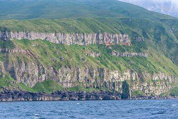 Massive horizontal ignimbrite (ash-flow) deposits form much of the SW part of Shiashkotan Island. (Photo: Tom Pfeiffer)