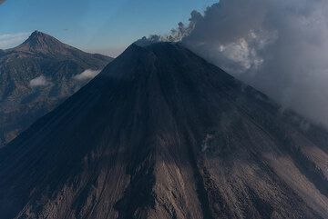The active lava flow (center) extending about half of the visible part of the cone. Summit of Nevado de Colima volcano in background. (Photo: Ingrid Smet)