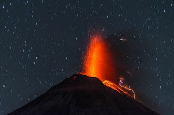 Lava-rich eruption early on 7 January with stars and a satellite trace. (Photo: Tom Pfeiffer)