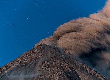 A few seconds exposure time blurs the ash plume drifting away from the crater to the SE. (Photo: Tom Pfeiffer)