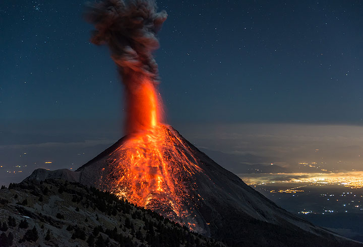 A strong eruption occurs on the evening of 25 Feb, producing a tall lava fountain from the northern vent and ejecting incandescent bombs to the lower northern flanks, where bush fires start to burn. The town of Colima in the background. (Photo: Tom Pfeiffer)