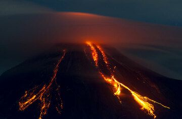 Glowing rockfalls from the (inactive, but still hot) southwestern lava lobe and the active southern lava flow on the evening of 13 July. (Photo: Tom Pfeiffer)