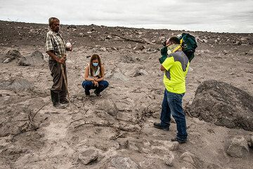 Antonio, whose land was invaded by the flow, explains journalists that below the surface, the deposit is still hot enough to burn wood. (Photo: Tom Pfeiffer)