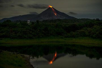 The volcano and its active lava flow mirrored in the lake. (Photo: Tom Pfeiffer)
