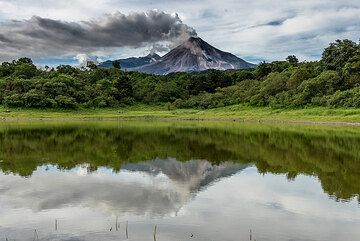 Steaming Colima volcano in Mexico with an active lava flow, mirrored in a small lake. (Photo: Tom Pfeiffer)