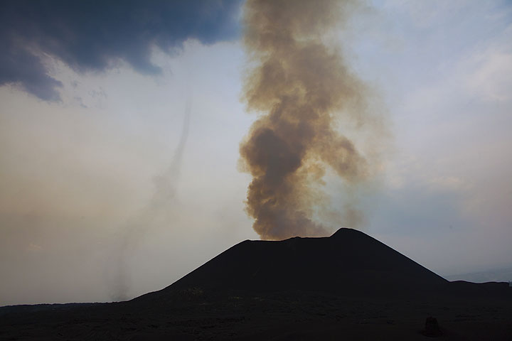 The active eastern cone of Kimanura. Hot rising air near the area where the lava tube begins at the base of the cone forms a small tornado. (Photo: Tom Pfeiffer)