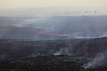 The desert of the active lava flow field, extending for many kilometers. Steam from burning forest in the far background. (Photo: Tom Pfeiffer)