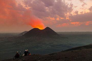 Just before sunrise, the sky is painted pink (Nyamuragira volcano eruption 2011-12) (Photo: Tom Pfeiffer)