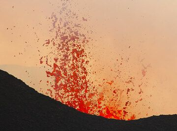 During phases of stronger degassing from the lava-filled vent inside the crater, lava bursts reach tens of meters above the crater rim. (Photo: Tom Pfeiffer)