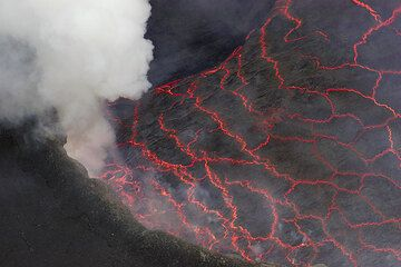 View onto the lava lake's surface during a calmer phase, showing the individual pieces of crust floating on the liquid lava lake. (Photo: Tom Pfeiffer)