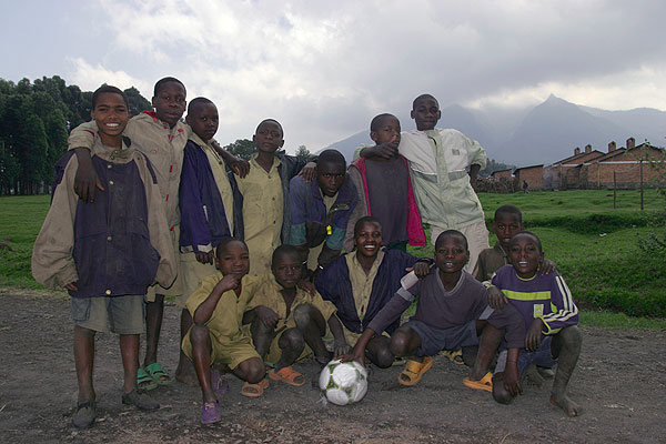 Group photo at the football field, Nyiragongo volcano looms in the background. (Photo: Tom Pfeiffer)