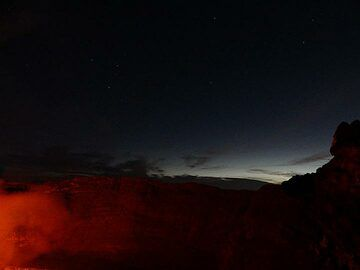 The lava lake´s red glow illuminates the steep  inner walls of Nyiragongo´s summit caldera whilst the sky to the east shows both the nightly stars and first morning light. (Photo: Ingrid Smet)