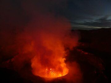 View onto the lava lake from Nyiragongo´s summit with the first day light appearing in the sky behind. (Photo: Ingrid Smet)