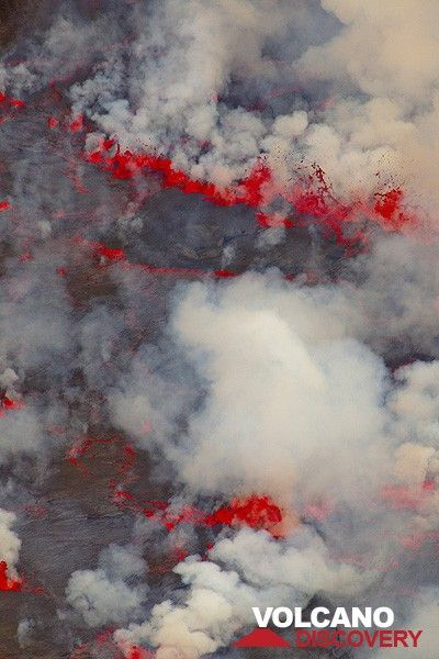 Red lava fountains and white plumes of gas alternate with dark areas of the thin, solid crust visible in between. (Photo: Tom Pfeiffer)
