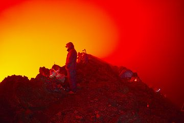 Watching the lava lake, the night is illuminated red by its glow. (Photo: Tom Pfeiffer)