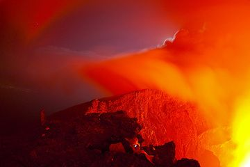 Nyiragongo volcano at night: Gilles in his favorite position, watching the fascinating movements of the lava lake at night for hours. The lights of Goma are visible in the far left. (Photo: Tom Pfeiffer)