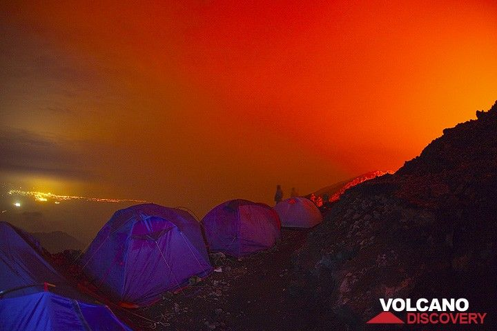 Our tents against the red sky and the lights of Goma town in the background. Two others are still awake, too, and visible as shadows behind the tents. (Photo: Tom Pfeiffer)