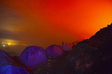 Nuestras tiendas contra el cielo rojo y las luces de la ciudad de Goma en el fondo. Otros dos son aún despiertos, demasiado y visible como sombras detrás de... (Photo: Tom Pfeiffer)