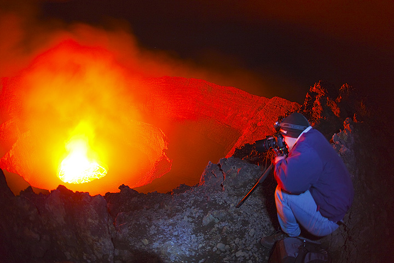 Photographer Franz studies the light of the lava lake.  (Photo: Tom Pfeiffer)