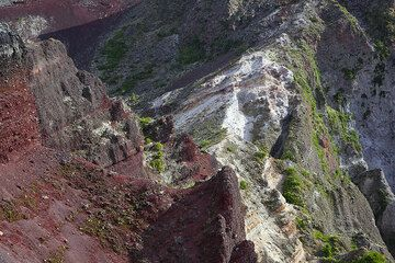 Red scoria and white pumice deposits in the colorful crater walls of Mt Tarawera volcano. (Photo: Tom Pfeiffer)