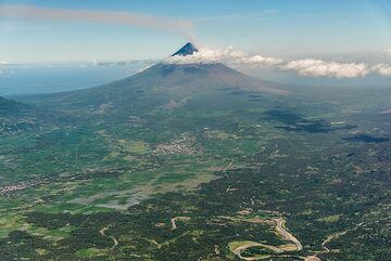 A light ash plume can be seen rising from the top of the volcano where the active vent of the 2018 eruption lies. The volcano forms a prominent landmark, rising to 2462 m elevation from near sea level out of the otherwise flat landscape of the Albay Gulf. (Photo: Tom Pfeiffer)