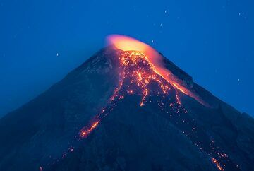 Zoom onto the upper part of Mayon, where the active lava flow can be seen splitting into 3 flows (the eastern one into the Basud gully is hidden behind the ridge on the upper flank right below the crater, visible by the glow) (Photo: Tom Pfeiffer)