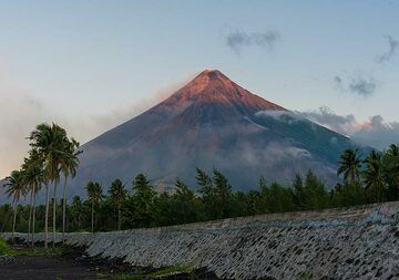 The first sunrays kiss the volcano's summit. this zone is occupied by dense and vast palm groves, a major crop of the local economy. (Photo: Tom Pfeiffer)