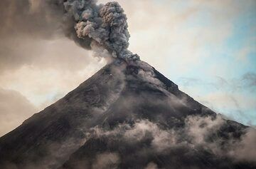 As it gets evening, the volcano clears up a bit; the first glowing bombs can be seen when enlarging the picture of the ash plume. (Photo: Tom Pfeiffer)