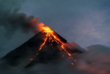 However, as night falls, explosions more or less cease and clouds play with the volcano. (Photo: Tom Pfeiffer)