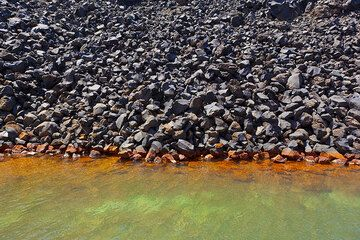 Block lava flow in a bay on Nea Kameni island (Santorini), where submarine hydrothermal springs deposit greenish iron mud, which oxidizes to orange near the surface. A great and utterly bizarre natural spa! (Photo: Tom Pfeiffer)