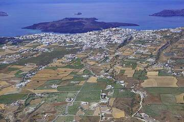 Fira town at the caldera rim and Nea Kameni island behind inside the caldera of Santorini. (Photo: Tom Pfeiffer)