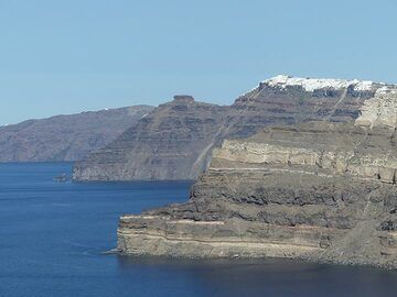 View from the port towards the beautifully coloured volcanic layers that make up the inner caldera wall and the remains of the Skaros shield left of the white houses of Imerovigli. (Photo: Ingrid Smet)