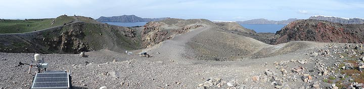 Panoramic view of the central area of Nea Kameni with eruption and explosion craters, monitoring equipment (front left) and a red-oxidised lava dome and flow (right). In the background one sees that caldera with (from left to right) the island of Therasia and the white villages of Oia and Fira on the island of Thera. (Photo: Ingrid Smet)