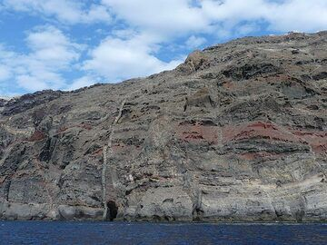 The colourful layers that make up the caldera cliffs are crosscut by volcanic dykes - sheets of now solidified lava that once rose up through the cracks in the caldera walls. (Photo: Ingrid Smet)