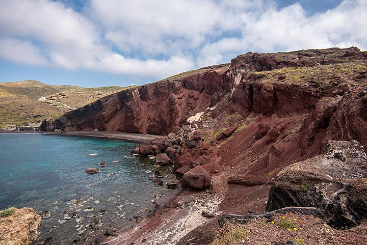 """The """"red beach"""" is a perfect example of an eroded cinder cone from a small flank eruption about 5-400,000 years ago. Erosion by the sea has cut through its center, allowing one to now study its architecture: layers of lapilli & lava bombs, small lava flows, the central dike. (Photo: Tom Pfeiffer)"""