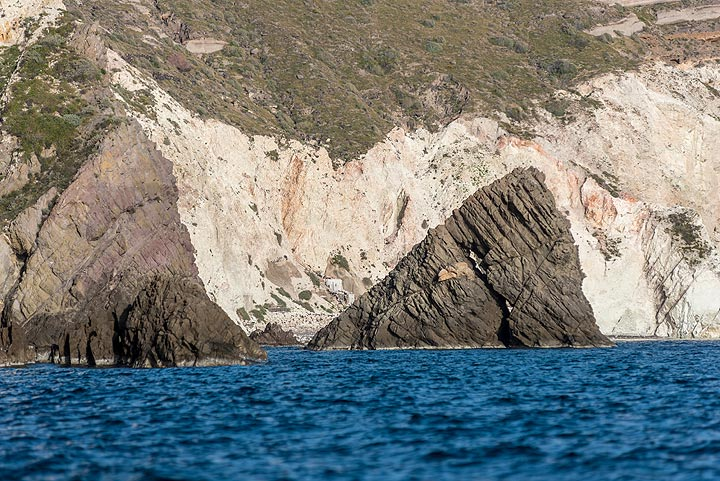 After some swimming, we return by boat. The black rocks are part of an andesitic (?) intrusion that domed up sea sediments. (Photo: Tom Pfeiffer)