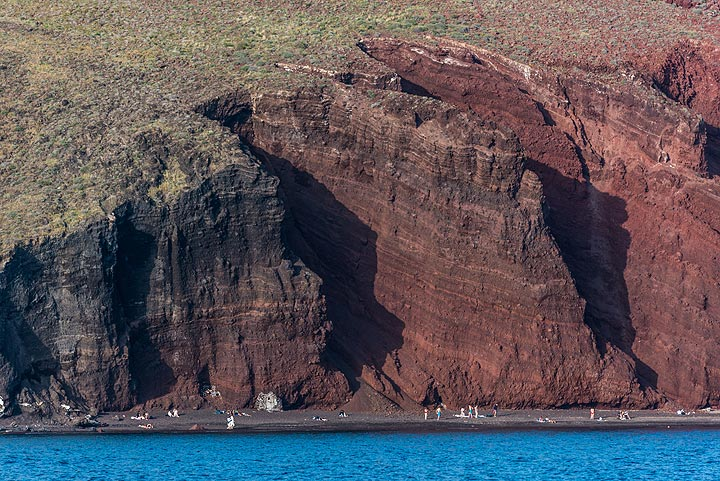 Approaching the red beach. To the left, further from the vent, oxidation of iron-bearing minerals has been less intense, which is why the color of the lava fragments gradually changes from red to black. (Photo: Tom Pfeiffer)